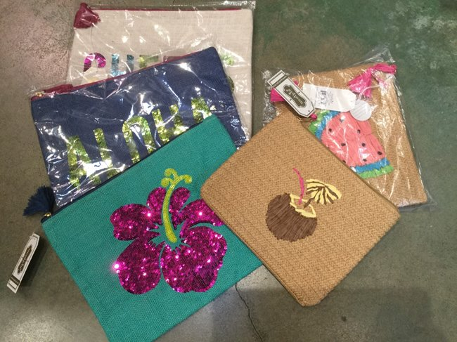 Various aloha-themed clutches available at Sunshine Swimwear in Waikiki Beach Walk® as a gift with purchase.