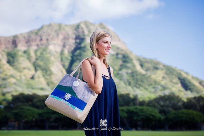Woman in a blue dress caring a quilted tote bag with a Diamond Head design while standing in front of real-life Diamond Head.