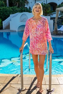 Blonde model standing in front of a swimming pool wearing a bright pink & orange floral tunic