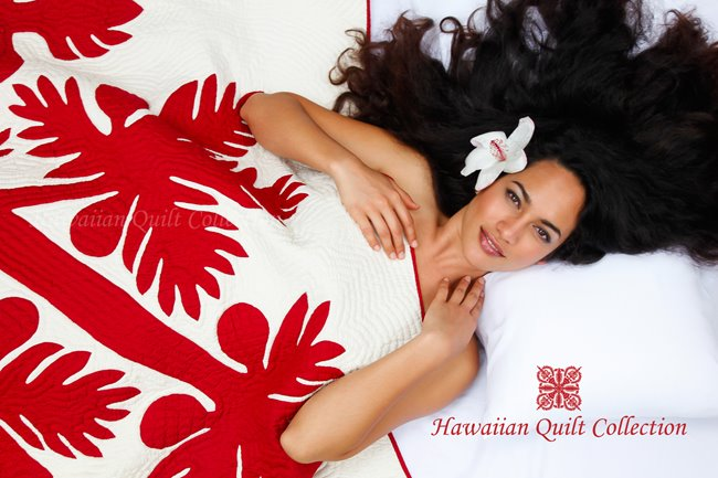 Brunette woman with a flower in her hair under a red & white Hawaiian quilt.