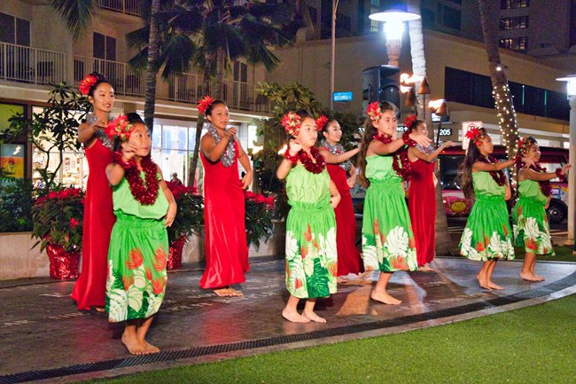 Group of hula dancers performing for an audience on the lawn in Waikiki.