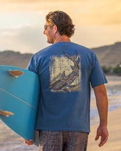Man holding a surfboard at the beach & wearing a blue shirt with a tribal shark design on the back