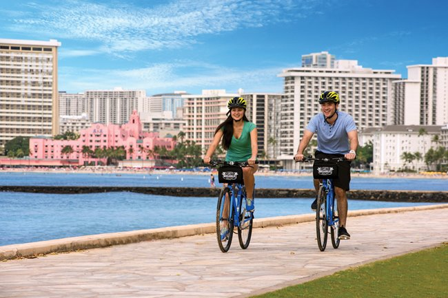 Couple biking along Waikiki with the ocean and the pink Royal Hawaiian Hotel in the background.