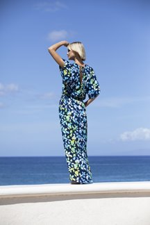 Blonde model looking out to the ocean while wearing a floor-length blue & green sleeved dress