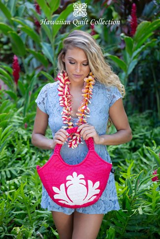Woman wearing a lei and holding a pink quilted handbag.
