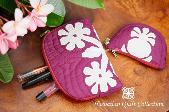 2 pink quilted makeup bags with Hawaiian motifs.