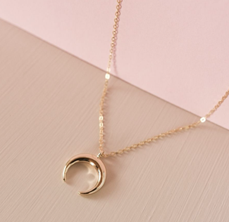 Gold chain necklace with a crescent moon pendent on a blush pink table