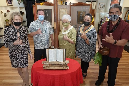 Group of people standing around an open book on display with various other Hawaiian cultural artifacts in The Royal Room at Waikiki Beach Walk.