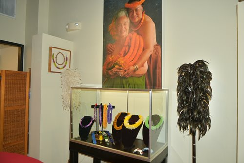 Display case of multicolored Hawaiian feather leis under a large portrait of Aunty Mary Lou of Hawaiian craft shop, Nā Lima Mili Hulu Noʻeau.