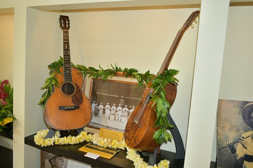 2 guitars propped up on either side of a photo of the string ensemble of the Royal Hawaiian Band in 1934.