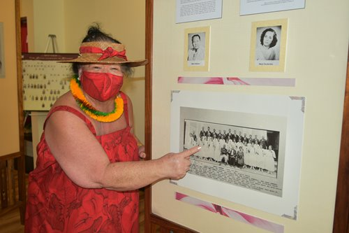 A woman in a red muumuu, mask, hat & lei pointing at a black & white photo on one of the Hawaiian culture displays.