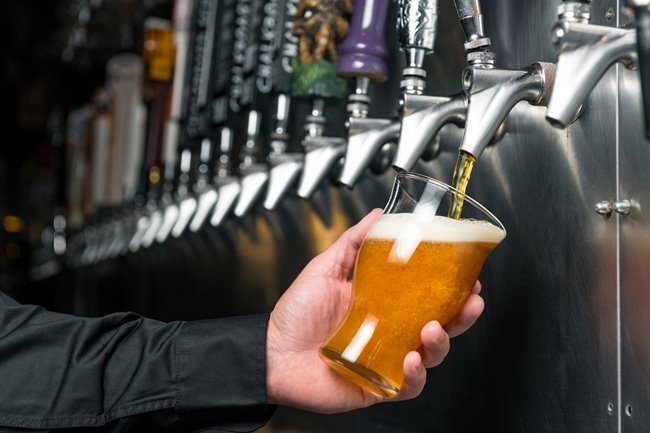 A glass of Yard House's 23rd anniversary beer being poured from draft