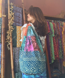Female model carrying blue & pink bag with multiple tapa patterns