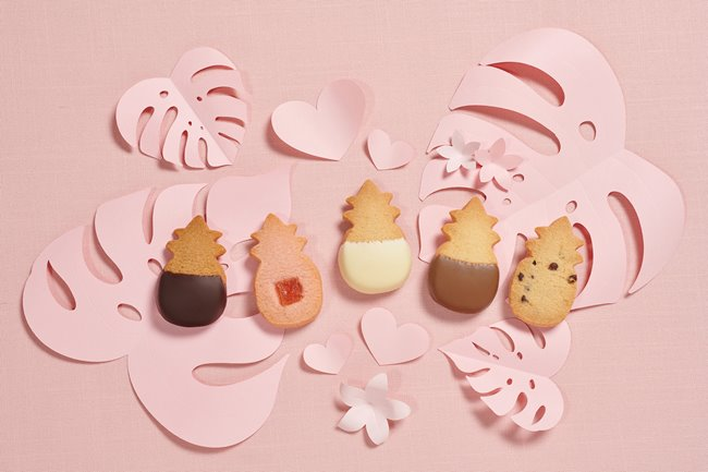 5 Honolulu Cookie Company pineapple-shaped shortbreads on pale pink cutouts of tropical leaves.