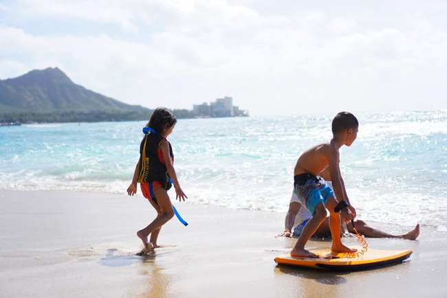 2 young children playing on a Hawaii beach in front of Diamond Head