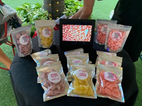 Different flavors of packaged hard candy on a table at the Beach Walk farmers market in Waikiki.