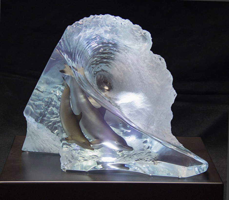 A sculpture of 3 dolphins swimming in a clear wave.