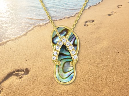 Single slipper with diamond straps & abalone body in front of a beach with footprints in the sand.