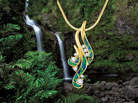 Gold waterfall pendant with opal inlays & diamonds in front of a real waterfall in Hawaii.