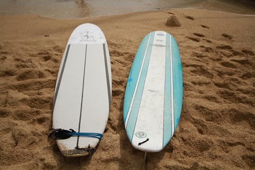 White and blue surfboards on the sand at the beach in Waikiki