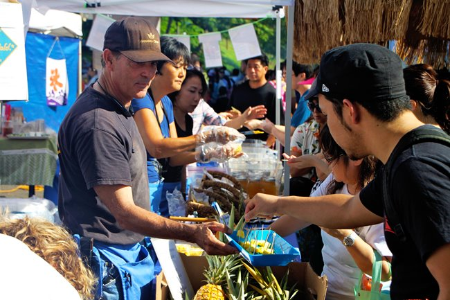 Local business owner offering samples of pineapple to customers at a farmers market in Waikiki