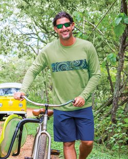 Man wearing a green long sleeve while standing next to a bike in the forest