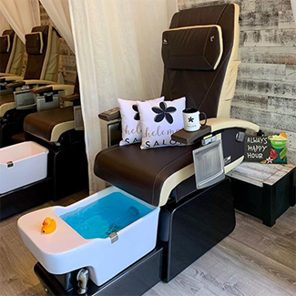 Brown pedicure chair with Hele Mai Salon branded pillows and mug in Waikiki